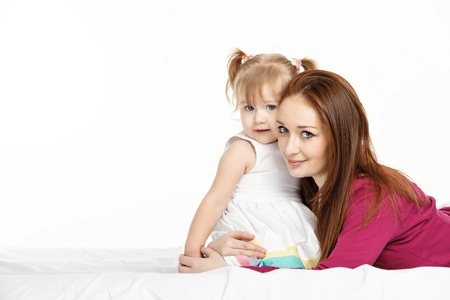 kids having fun: Happy woman and young girl (child)smiling in bed. Mother day concept Stock Photo