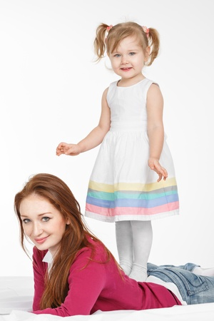 Happy woman and young girl (child)smiling in bed. Mother day concept photo