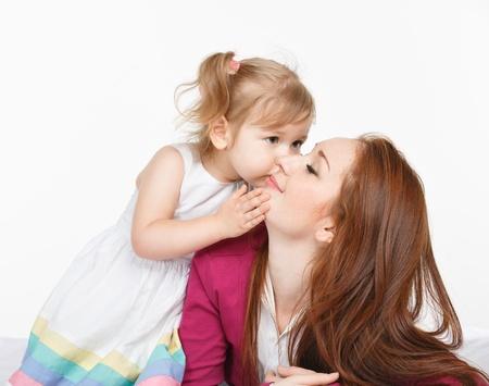 幸せな女とベッドの中で笑っている若い女の子 (子)。母の日の概念