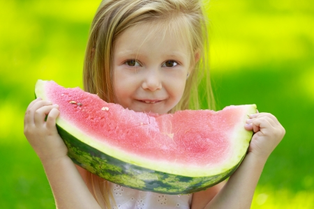 family picnic: Happy smiling child sitting on green grass in park and eating watermelon