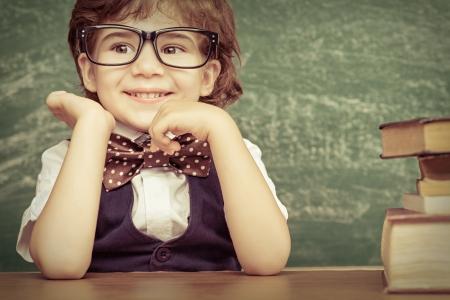 陽気な笑みを浮かべて男の子はテーブルに座っています。カメラの概念は学校を見てください。
