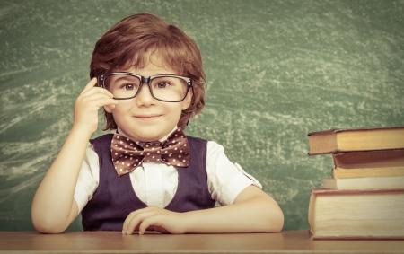 Sorriso alegre garotinho sentado à mesa. Olhando para a câmera conceito Escola