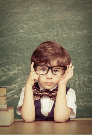 테이블에 앉아 명랑 웃는 어린 소년. 카메라 학교 개념을 살펴보면