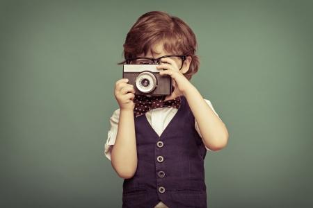 インスタント カメラを保持している陽気な笑みを浮かべて子供 (男の子)