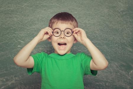緑の背景に陽気な笑みを浮かべて男の子。 写真素材
