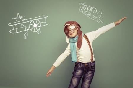 緑の背景にヘルメットで陽気な笑みを浮かべて子供 (男の子) l。ビンテージ パイロット (アビエイター) コンセプト 写真素材