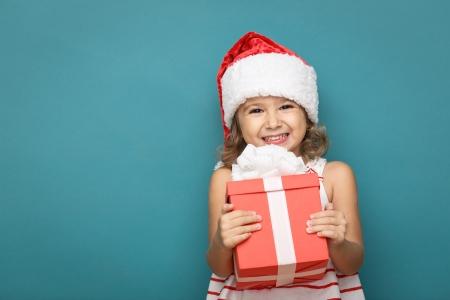 Menina de sorriso pouco feliz com caixa de presente de Natal.