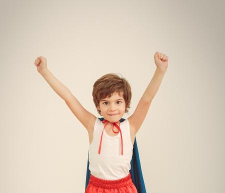 Funny little power super hero child (boy) in a blue raincoat.  photo