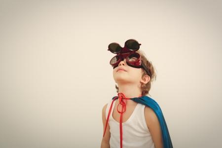Engraçado pouco poder de super-herói criança (menino) em uma capa de chuva azul. Imagens