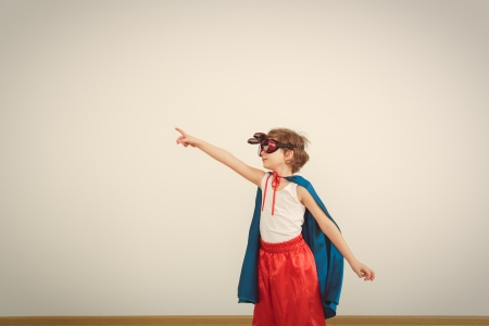 Funny little power super hero child (boy) in a blue raincoat.  Stock Photo