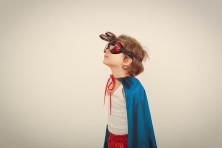 Funny little power super hero child (boy) in a blue raincoat.  Standard-Bild