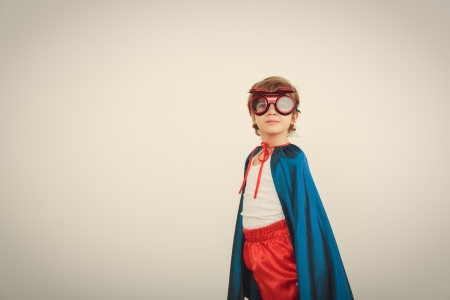 super red: Funny little power super hero child (boy) in a blue raincoat.