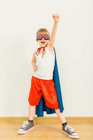bambini felici: Il piccolo bambino divertente super potere eroe (ragazzo) in un impermeabile blu. Concetto di supereroe