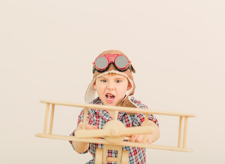Cheerful smiling kid  boy l in helmet on a green background  Vintage pilot  aviator  concept photo