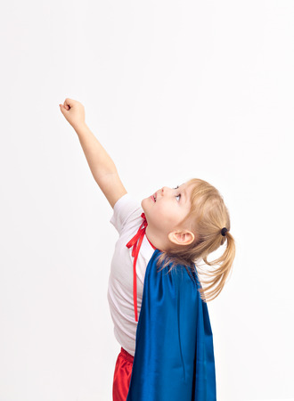 Funny little power super hero child (girl) in a blue raincoat.  Superhero concept photo