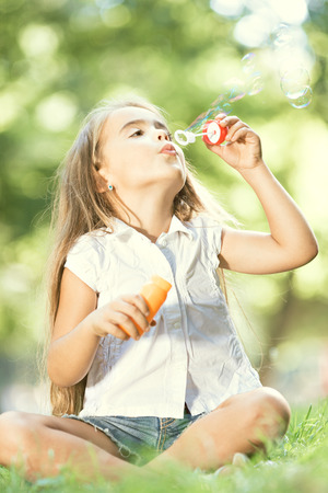 girl blowing: Little happy girl blowing soap bubbles in the parc