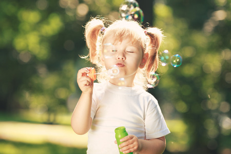 blowing bubbles: Little happy girl blowing soap bubbles in the parc