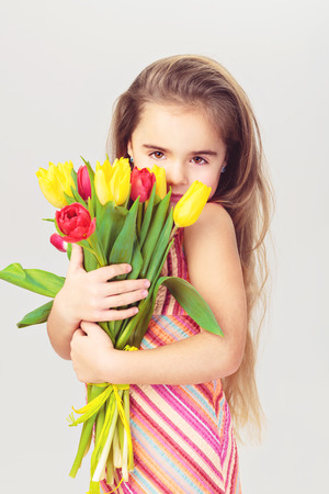 Fashion baby face beautiful child with fair hair in a pink dress holds flowers photo