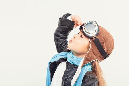 비행기와 재생 흰색 배경에 헬멧에 아름 다운 웃는 아이 (아이, 소녀). 빈티지 파일럿 (조종사) 개념 스톡 콘텐츠