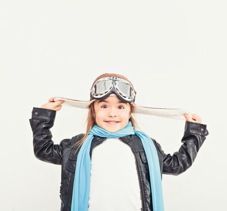 美しい笑顔の子供子供 (女の子) ヘルメット平面で遊んで白い背景の上。ビンテージ パイロット (アビエイター) コンセプト