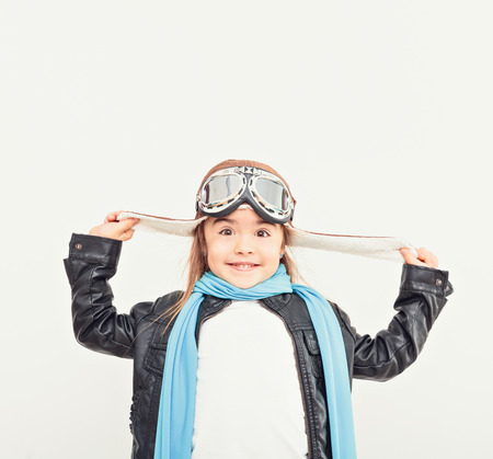 Beautiful smiling child (kid, girl) in helmet on a white background playing with a plane. Vintage pilot (aviator) concept