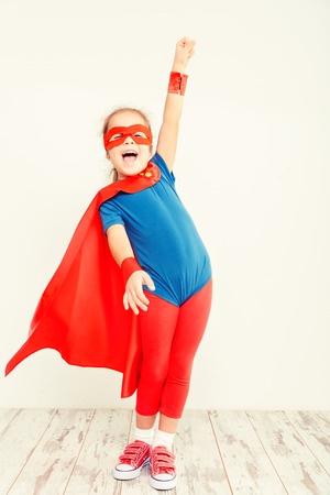 vintage children: Funny little power super hero child (girl) in a blue raincoat. Superhero concept Stock Photo