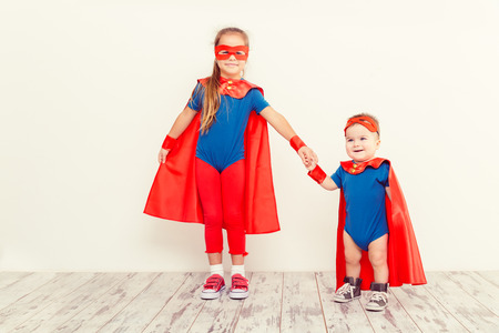 Two funny little power super hero kids in a blue raincoat. Superhero concept photo