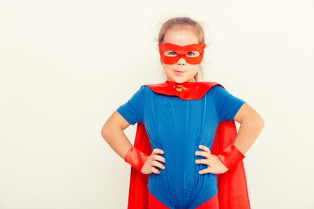 Funny little power super hero child (girl) in a blue raincoat. Superhero concept Stock Photo