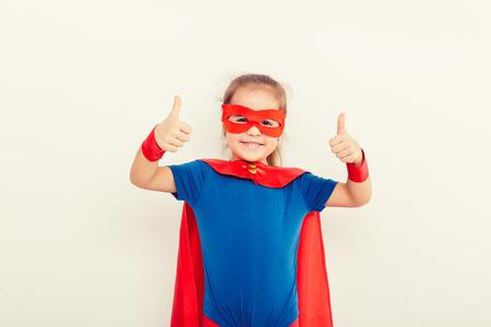 Funny little power super hero child (girl) in a blue raincoat. Superhero concept Standard-Bild