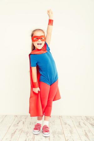 Pouco poder de super-herói engraçado criança (menina) em uma capa de chuva azul Imagens