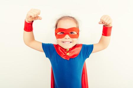 面白いパワー スーパー ヒーローで小さな子供 (女の子) 青いレインコート 写真素材