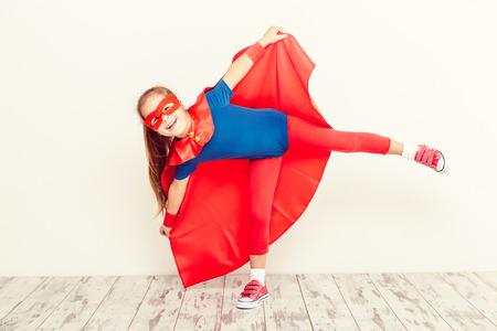 面白い少し力スーパー ヒーローの子供 (女の子) 青いレインコートで 写真素材