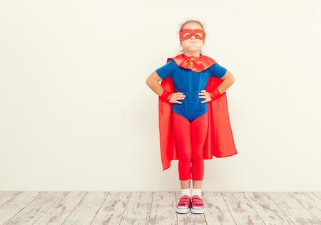 Funny little power super hero kid (girl) in a blue raincoat Stock Photo