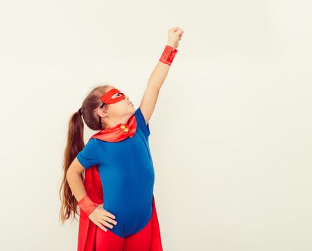 Funny little power super hero kid (girl) in a blue raincoat Standard-Bild