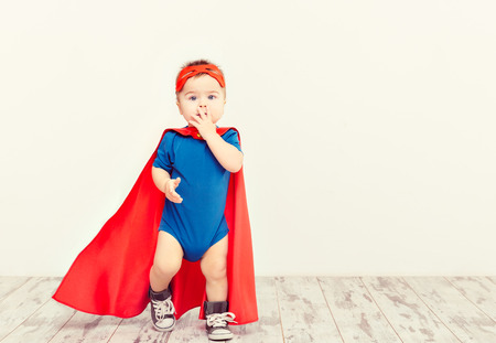 Funny little power super hero child (boy) in a blue\ raincoat