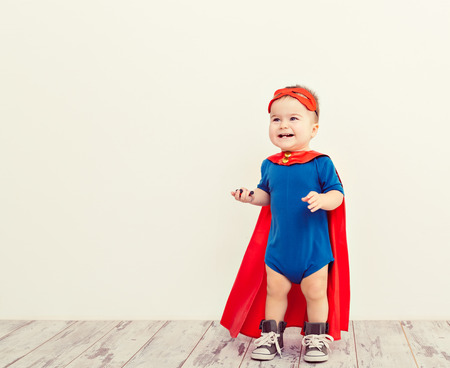 面白いパワーのスーパー ヒーローで小さな子供 (少年) 青いレインコート