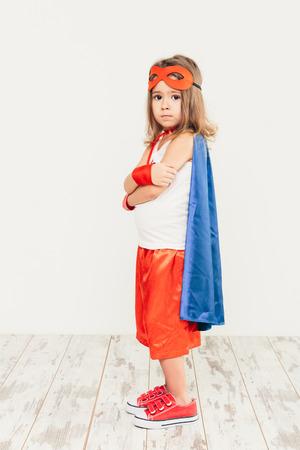Funny little power super hero child (girl) in a blue raincoat. Superhero concept photo