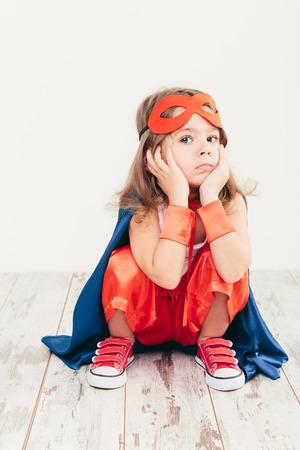 Funny little power super hero child (girl) in a blue raincoat Standard-Bild