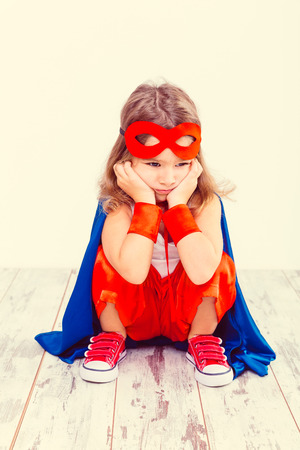 Funny little power super hero child (girl) in a blue raincoat Stock Photo