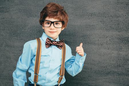 명랑 칠판에 작은 아이 (소년) 고. 카메라를 찾고 있습니다. 학교 개념