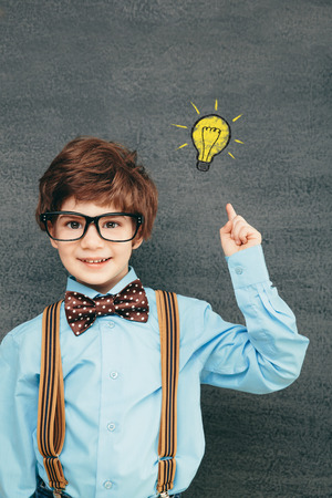 Cheerful smiling little kid (boy) against  chalkboard; raised his hand up. Looking at camera. School concept Stock Photo