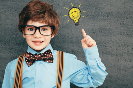 Cheerful smiling little kid (boy) against  chalkboard. Looking at camera. School concept Stock Photo