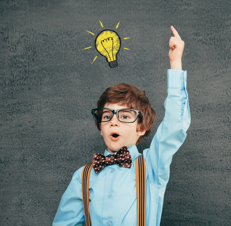 Cheerful smiling little kid (boy) against  chalkboard; raised his hand up. Looking at camera. School concept photo