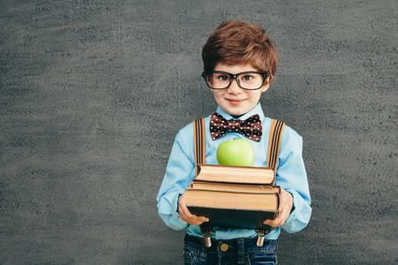 小さな子供 (男の子) 黒板に対して笑みを浮かべて元気。カメラを見ています。学校コンセプト