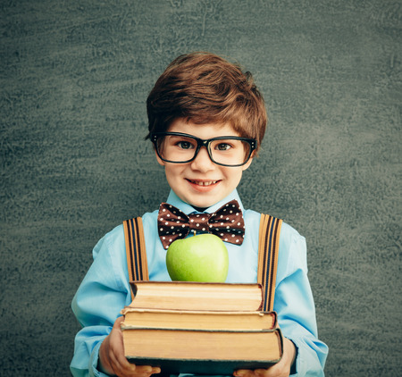 Cheerful smiling little kid (boy) against  chalkboard. Looking at camera. School concept Standard-Bild