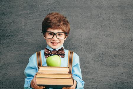元気黒板に対して小さな子供 (男の子) の笑みを浮かべてします。カメラを見てください。学校概念