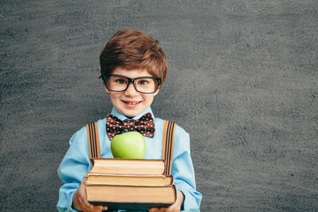 칠판에 명랑 웃는 어린 아이 (소년). 카메라를 찾고 있습니다. 학교 개념