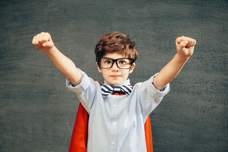 Cheerful smiling little kid (boy) against  chalkboard raised his hands up.  School and superhero concept