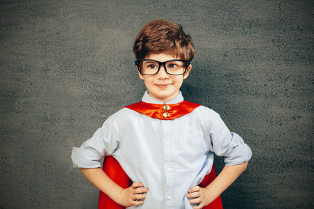 Cheerful smiling little kid (boy) against  chalkboard.  School and superhero concept photo