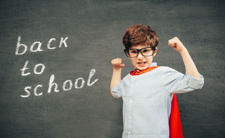 funny kid: Cheerful smiling little kid (boy) against  chalkboard raised his hands up.  School and superhero concept